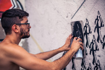 Graffiti artist painting a wall in the street