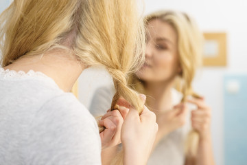 Woman making braid on blonde hair