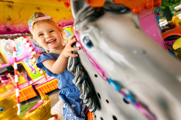 Fotobehang Amusementspark happy smiling little girl sitting on horse carousel at amusement park