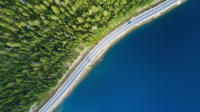 Beautiful aerial view of road between green summer forest and blue lake in Lapland. Car moving on road.