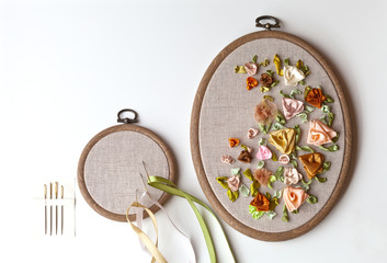 Handmade embroidery satin ribbons with flowers ornament on linen canvas in plastic hoop and special needles with a big eyelet (embroidery made by the author of the photo). Copy space, flat lay