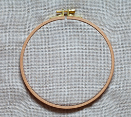 Special cloth with square mesh pattern linen canvas on the wooden hoop for cross-stitch embroidery or embroidery with satin ribbons. Template for text or advertising sewing and needlework