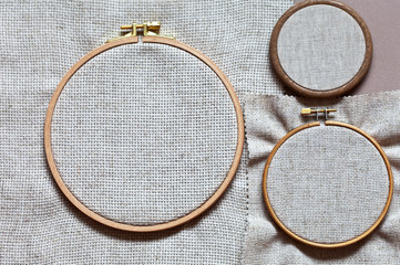 Folding round hoops for hand embroidery with natural unpainted linen canvas of different density. Handicraft and hobby accessories