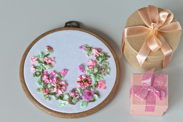 Hand embroidered flower ornament with satin, silk and nylon ribbons on the hoop for a birthday gift and a boxes with presents (the embroidery was made by the author of the photo)