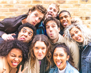 Multiracial friends taking selfie and making funny faces