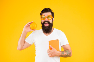 Total orange. Man bearded cheerful smiling hipster wear orange color sunglasses while hold orange fruit and book notepad. Guy long beard likes orange color. Vitamin source. Bright and vibrant