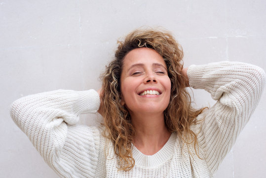 Close up happy middle age woman smiling with eyes closed and hands behind head against white background
