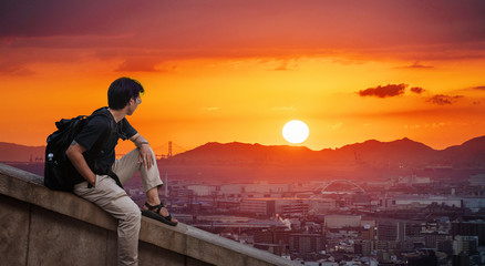 Wall Mural - a man with backpack looking at Osaka city view in sunset with the sun