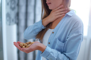 Young woman suffers from choking and cough from allergic reaction to peanut. Danger of nuts and food allergy