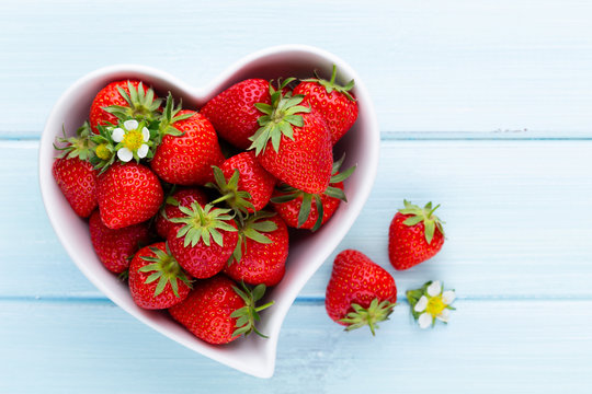 Strawberry heart. Fresh strawberries in plate on white wooden table. Top view, copy space.