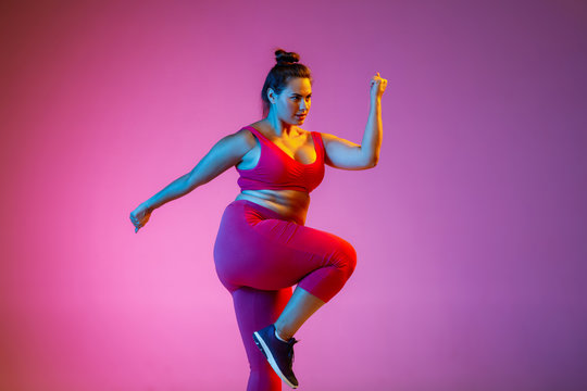 Young caucasian plus size female model's doing exercises on gradient purple background in neon light. Cardio training, jumping. Concept of sport, healthy lifestyle, body positive, equality.