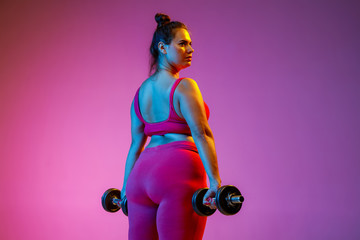 Young caucasian plus size female model's doing exercises on gradient purple background in neon light. Training her upper body with the weights. Concept of sport, healthy lifestyle, body positive.