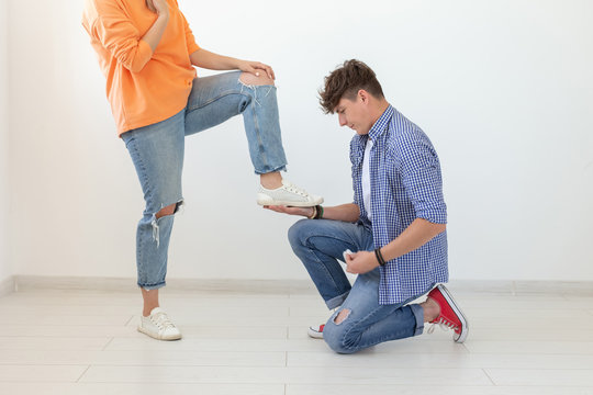 Young man is kneeling and reverently tying shoelaces to his domineering unidentified woman posing on a white background. Concept of dominant relationships.