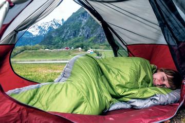 girl sleeps in sleepbag in the tent
