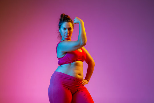 Young caucasian plus size female model's doing exercises on gradient purple background in neon light. Showing muscules. Concept of sport, healthy lifestyle, body positive, equality, women's rights.