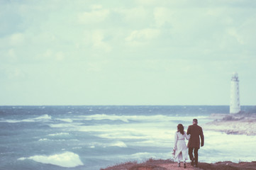 vintage picture of young couple in autumn coat walking along stormy windy sea shore with high waves and lonely lighthouse on edge of the world with copy space