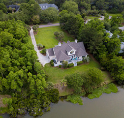 Aerial view of expensive waterfront home on wooded lot.