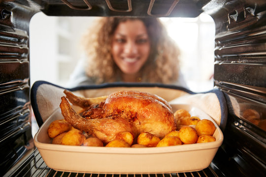 View Looking Out From Inside Oven As Woman Cooks Sunday Roast Chicken Dinner