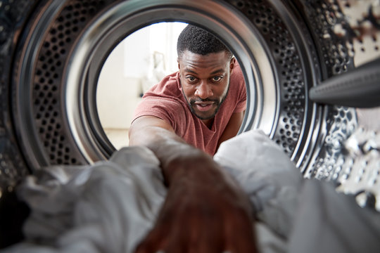 View Looking Out From Inside Washing Machine As Man Does White Laundry