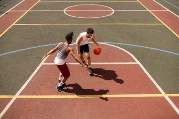 Young basketball player trying to defend ball from rival while carrying it