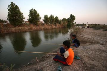 Children fish in the Jassim river near Basra