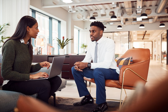 Businesswoman Interviewing Male Job Candidate In Seating Area Of Modern Office