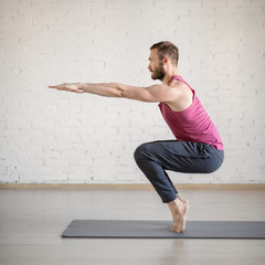Chair pose. Caucasian man stands on tiptoe and doing yoga in fitness studio, side view, selective focus.