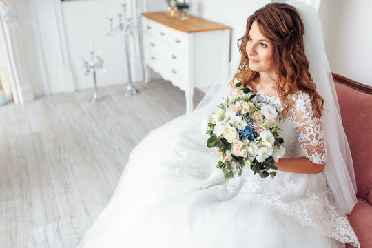 Beautiful bride in a wedding dress with lace, posing in the Studio