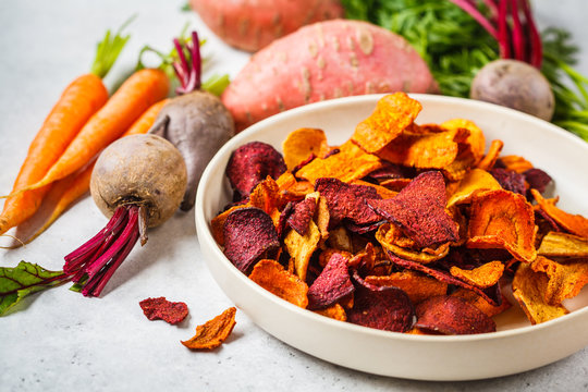 Bowl of healthy vegetable chips from beets, sweet potatoes and carrots on white background.