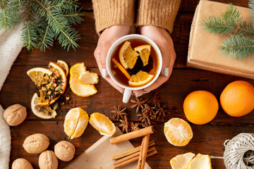 Top view of aromatic tea with orange slices held by female