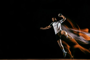 Fototapeta Caucasian young handball player in action and motion in mixed lights over black studio background. Fit male professional sportsman. Concept of sport, movement, energy, dynamic, healthy lifestyle. obraz