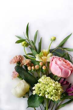 Vertical image of fresh cut flowers and greenery on a white background with copy space