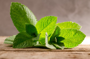 Fresh green peppermint leaves on a rustic wooden background.