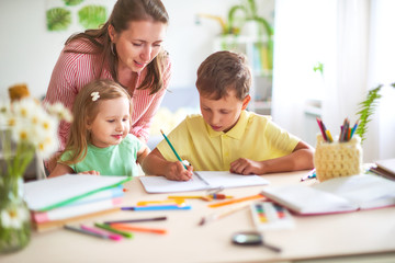 mother daughter and son draws pencil on a sheet of paper sitting at home at the table in a bright...