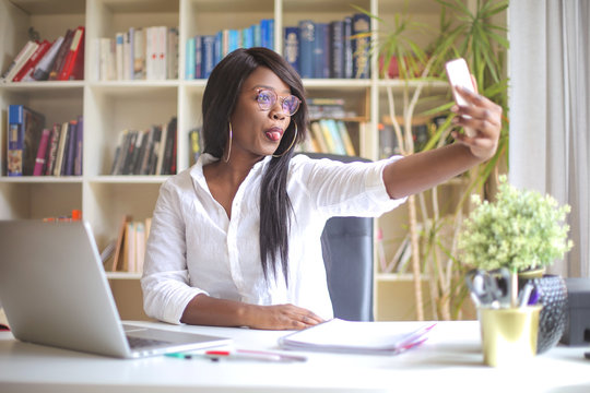 Funny woman making a selfie sitting at her desk