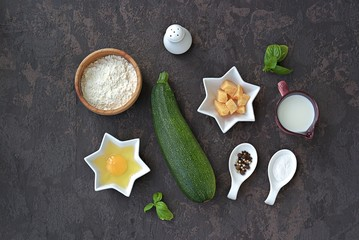 Ingredients for cooking zucchini wafers on a dark concrete background: fresh zucchini, cheese, milk, wheat flour, baking powder, salt, pepper. Top view, copy space. Italian food. Healthy food.