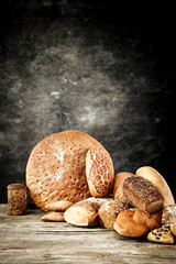 Photo sur Aluminium Boulangerie Rolls and braed on wooden table top and black wall.