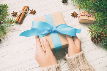 Wall Mural - Female hands holding handmade present box in recycled paper on white wooden table background. christmas preparation concept, Gift wrapping background. Toned
