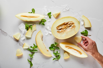 top view of cut delicious melon on marble surface with mint and ice near man hand