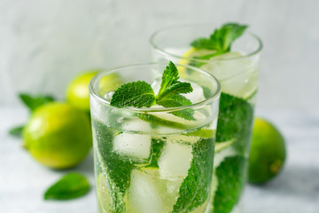 Fresh mojito cocktail with lime and mint in glass on concrete background. Cold refreshing drink. Selective focus.