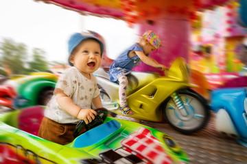 Deurstickers Amusementspark cheerful children in carousel at amusement park