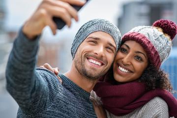 Smiling multiethnic couple taking selfie in winter