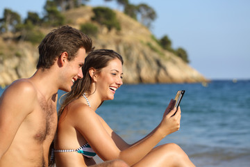 Happy couple on the beach checking tablet