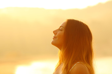 Profile of a woman at sunset breathing fresh air
