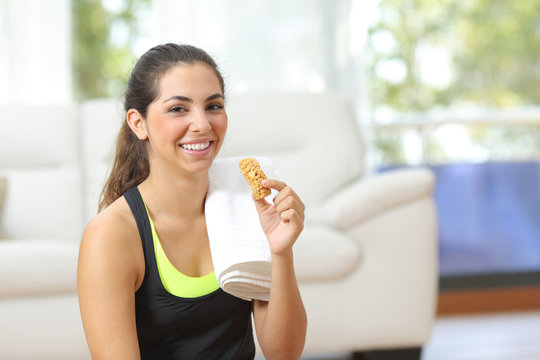 Woman holding an energy bar after sport at home