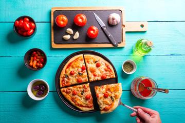 Pizza de Majericão sobre a mesa de madeira de cor turquesa com azeite, azeitonas pretas, orégano, molho de tomate
