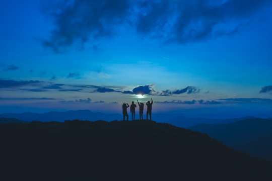 The four people standing on the beautiful mountain on the moon background