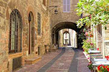 Fototapete - Beautiful arched street in the medieval old town of Assisi with flowers and restaurant tables, Italy