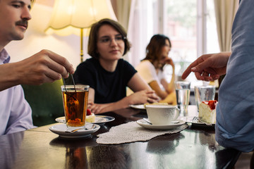 Tea Time - Young People Having Cake and Tea/Coffee