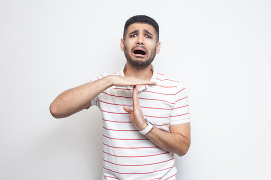 I need more time. Portrait of pleased handsome bearded young man in striped t-shirt standing with time out gesture and looking at camera pleading. indoor studio shot, isolated on white background.